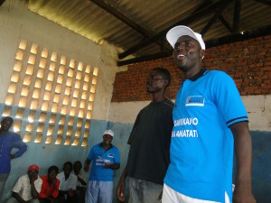 Emmanuel Ntakirutimana, right, stands with Jackson Nduwayo, a youth member of the ruling party, during a meeting where youth from opposing political parties come together to learn peacebuilding skills. As they learn to know each other and work, learn and play together, violence decreases in the community – even during this volatile post-election time. . (Photo courtesy of MIPAREC)